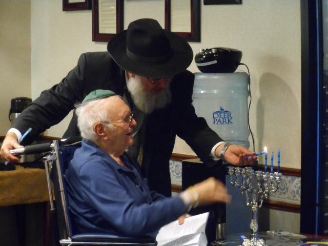 Rabbi Reichman helps a Regency Resident Light The Menorah!